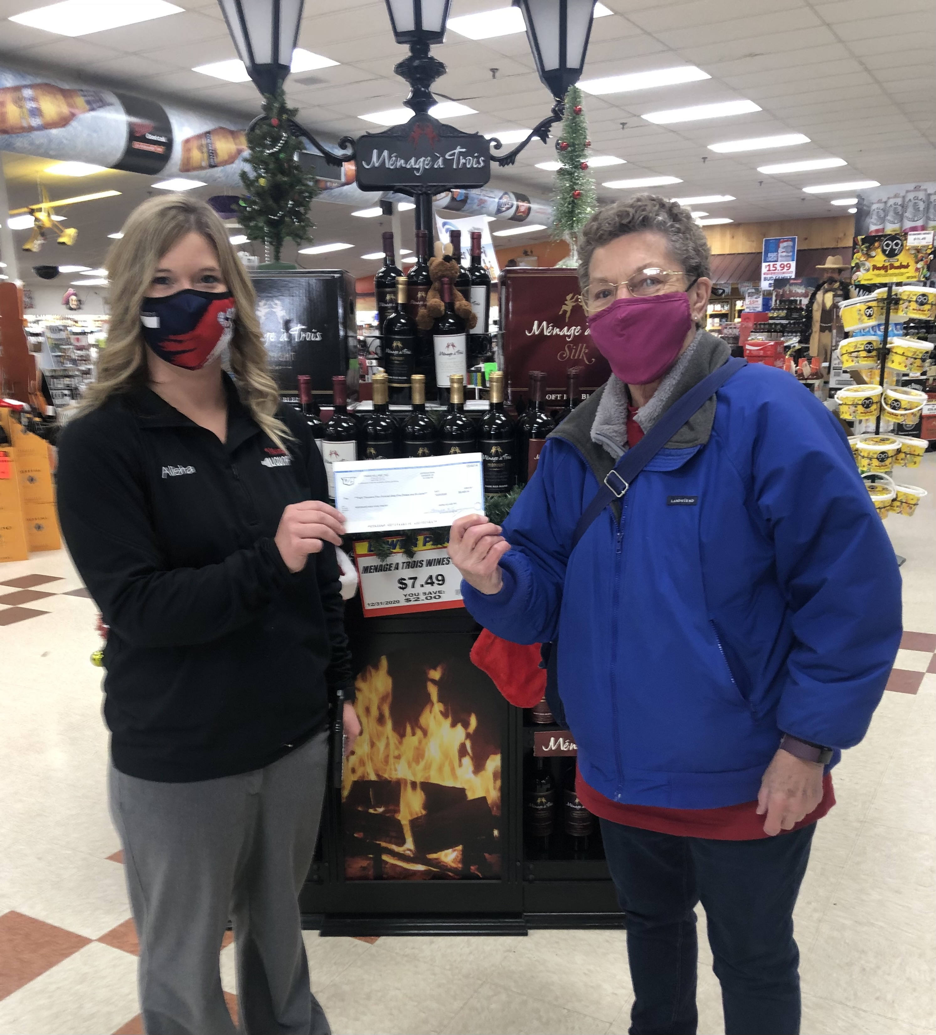 Viking Liquor Manager Alisha Johnson presents a $8,465 check to Reedsburg Area Food Pantry volunteer Ann Seamonson. The money was raised from Viking Liquor's online bourbon auction, which was held before the holidays in place of the usual annual Jingle Mingle. (Submitted photo)