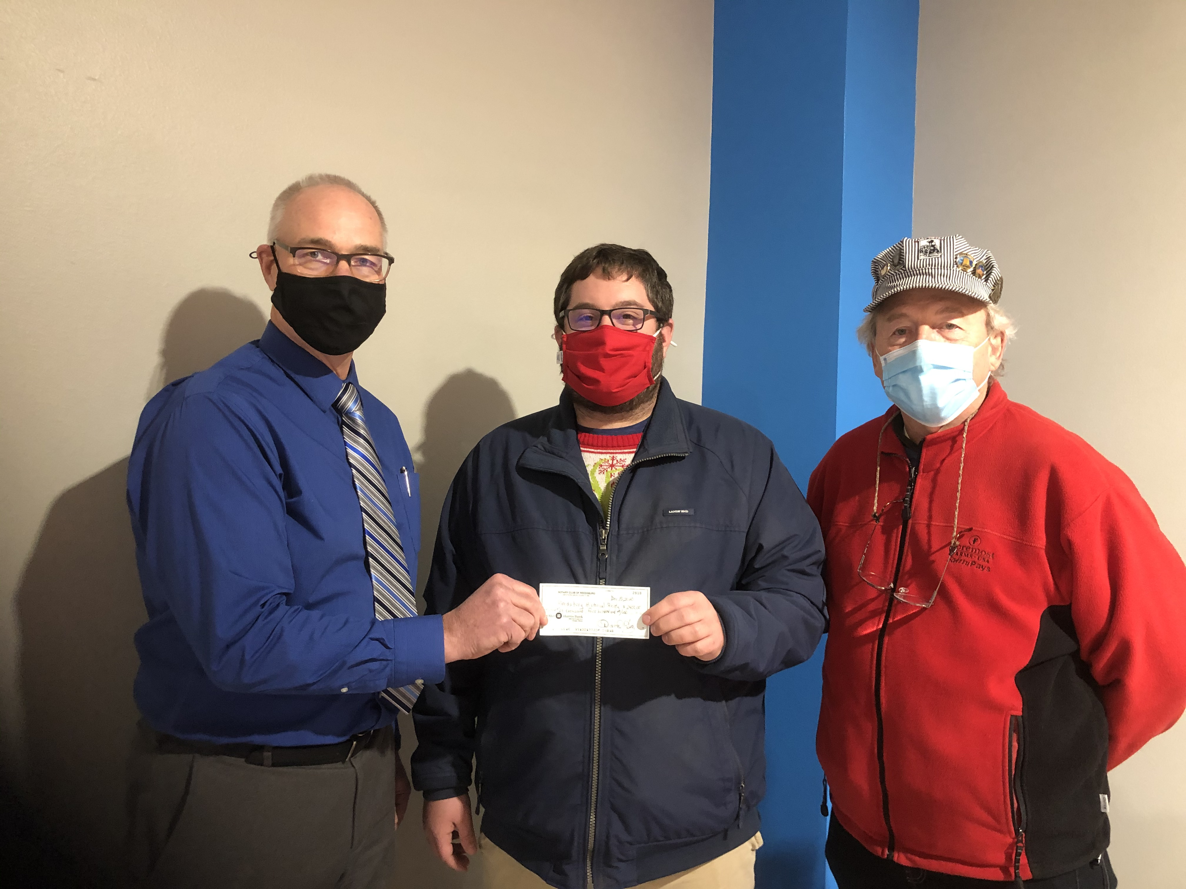 Joel Groskreutz, president of the Rotary Club of Reedsburg Western Sauk County, presents a $2,400 check to President Craig Braunschweig and Treasurer Lou Kirt of the Reedsburg Area Historical Society.